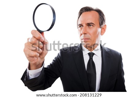 Businessman with magnifying glass. Concentrated mature man in formalwear looking through a magnifying glass while standing isolated on white background  - stock photo
