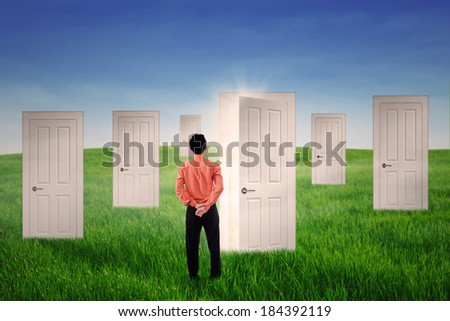 Businessman with many doors connecting to many opportunities - stock photo