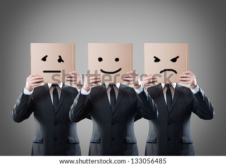businessman with mask of different emotions - stock photo