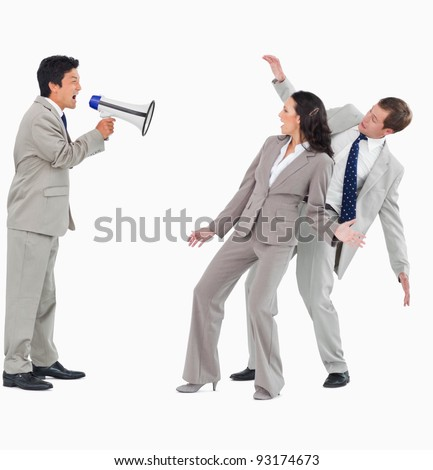 Businessman with megaphone shouting at colleagues against a white background - stock photo