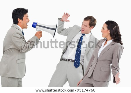 Businessman with megaphone yelling at colleagues against a white background - stock photo