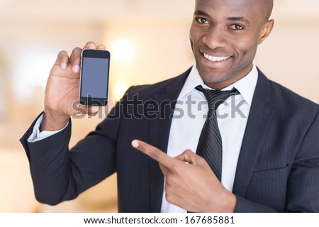 Businessman with mobile phone. Cheerful young African man in formalwear holding a mobile phone and pointing it - stock photo