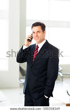 Businessman with mobile phone in office lobby