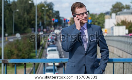 Businessman with mobile phone. In the background bustling street. - stock photo