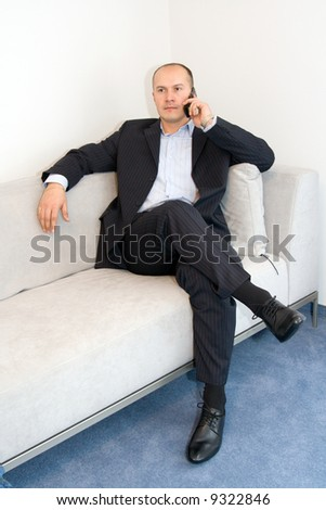 Businessman with mobile phone sitting at sofa