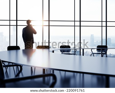 businessman with mobile phone standing in office - stock photo