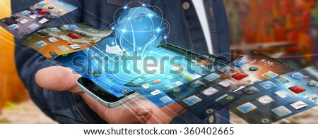 Businessman with modern mobile phone in his hand switching pictures - stock photo