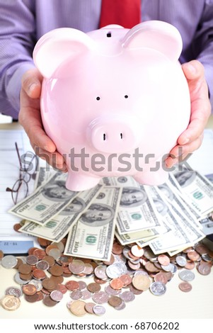 Businessman with money and a pink pig bank - stock photo