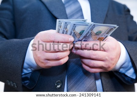Businessman with money in hand recalculates dividends - stock photo