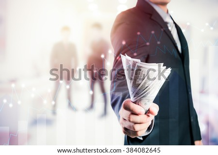 Businessman with money in hand, US dollar (USD) bills - investment, success and profitable business concepts.Forex graph on the business background. A metaphor of international financial consulting - stock photo