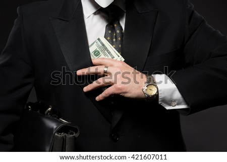 Businessman with money in studio. Currency bribing. Businessman hiding money in jacket pocket. Corruption and fraud concepts. - stock photo
