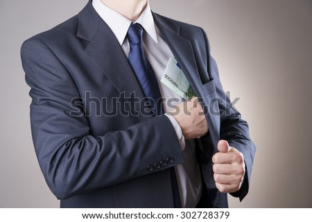 Businessman with money in studio on a gray background. Corruption concept - stock photo
