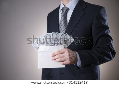 Businessman with money in studio on a gray background. Corruption concept. Hundred dollar bills - stock photo
