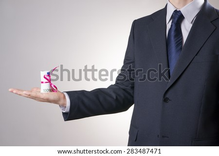 Businessman with money with bow in male hand on a gray background. Concept. - stock photo