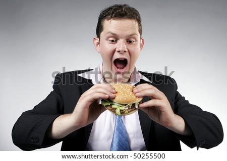 Businessman with mouth wide opened, ready to eat a burger - stock photo