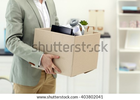 Businessman with moving box in office - stock photo