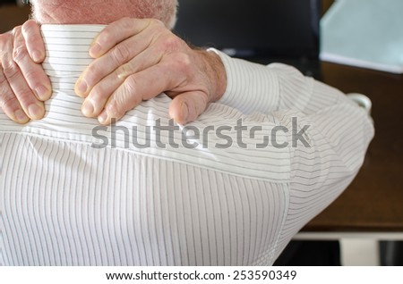 Businessman with neck pain at office