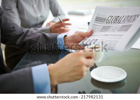 Businessman with newspaper having coffee at workplace - stock photo