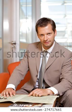 Businessman with newspaper, portrait - stock photo