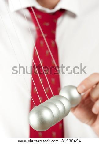 businessman with newton pendulum - stock photo