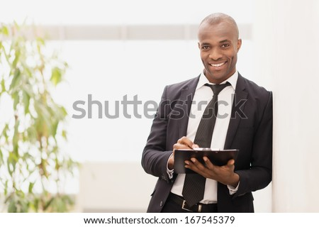Businessman with note pad. Cheerful young African businessman writing something in his note pad and smiling at camera - stock photo