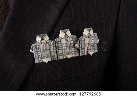 businessman with one dollar bill folded origami into a t-shirt in suit pocket - stock photo