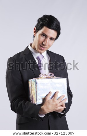 Businessman with one gift package (isolated on gray) - stock photo