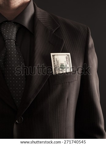 Businessman with one hundred dollars bill in his jacket pocket. - stock photo