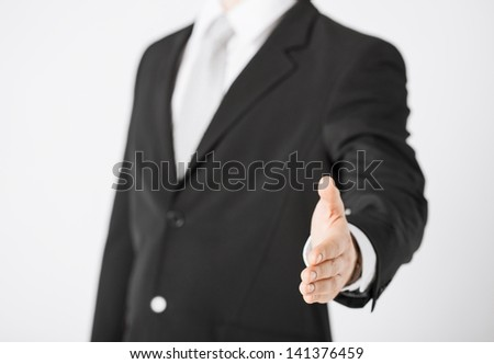 businessman with open hand ready for handshake - stock photo