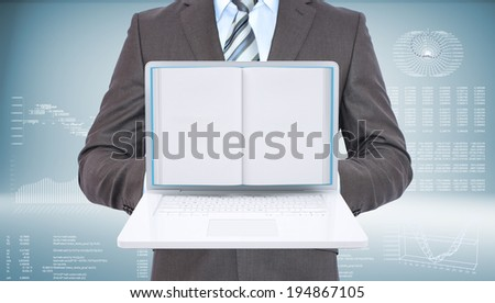 Businessman with open laptop and book. High-tech graphs at backdrop - stock photo