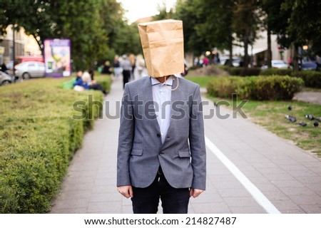 Businessman with paper bag on the head in the street