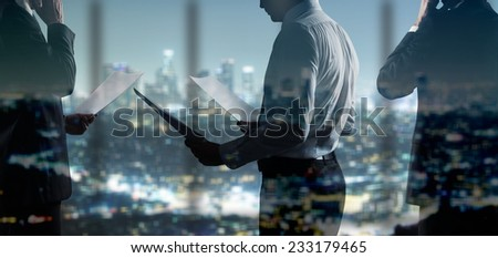 businessman with paper standing in night office - stock photo