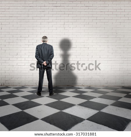 businessman with pawn shadow on a chess board - stock photo