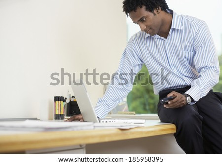 Businessman with PDA using laptop - stock photo