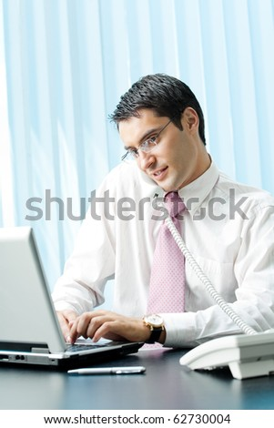 Businessman with phone and laptop at office