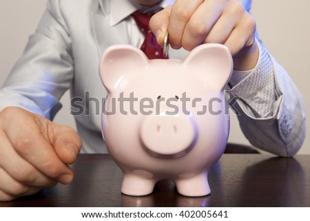Businessman with pink piggy bank and coin - stock photo