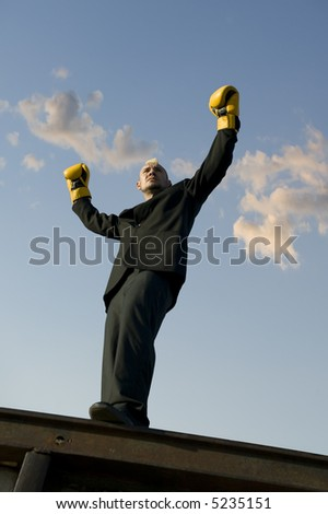 Businessman with punk hairdo and boxing gloves stands victorious with his arms in the air.. - stock photo