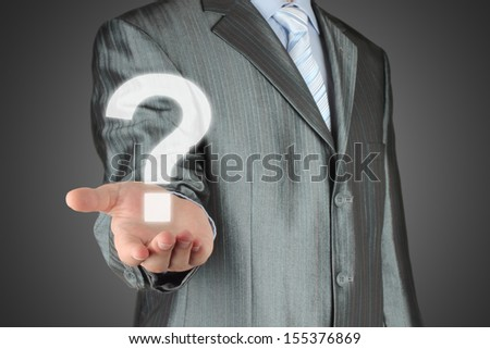 Businessman with question mark on dark background  - stock photo