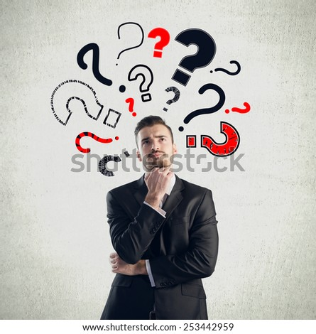 Businessman with question marks - stock photo