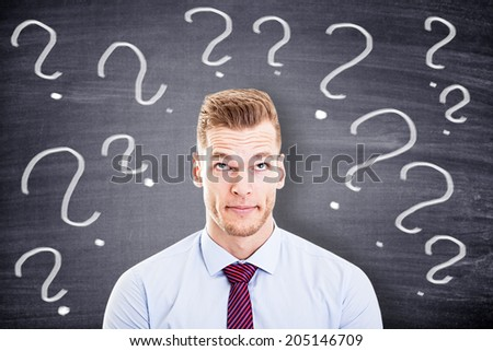 businessman with question marks in front of a blackboard  - stock photo