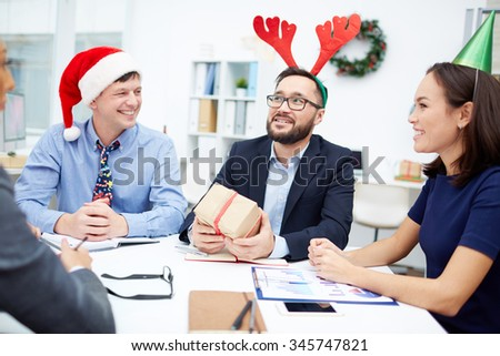Businessman with red deer horns guessing what gift-box contains among his colleagues in office