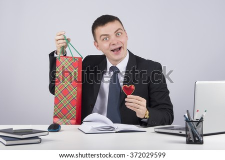 Businessman with red heart - customer relationship management on gray background