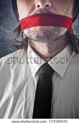 Businessman with red strip over mouth. Silence and secrecy concept. - stock photo