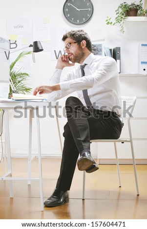 Businessman with rimmed glasses looking at computer./ Young businessman talking on smartphone in office - stock photo