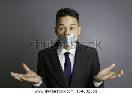 Businessman with silver tape over his mouth and hands up, conceptual image, restriction, silence, frightens, eyes wide open, formal, isolated on gray background, studio shoot.