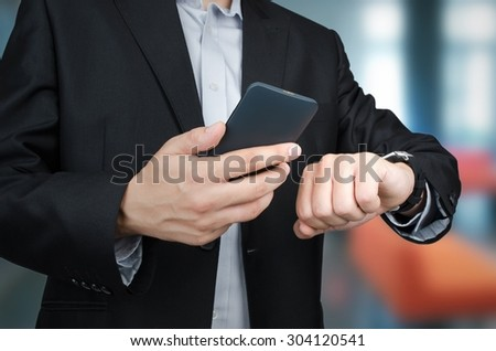 Businessman with smartphone and smartwatch working in office