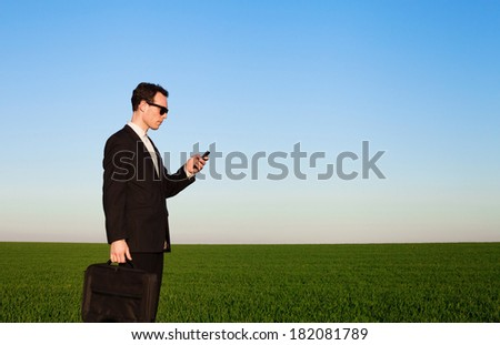 businessman with smartphone in green field