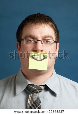 Businessman with smiley yellow sticky note on face - stock photo