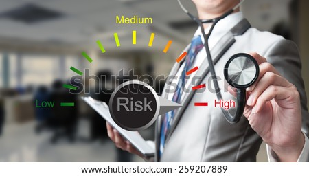 businessman with stethoscope working on risk management, business concept - stock photo