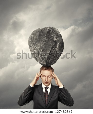 businessman with stone on his head - stock photo